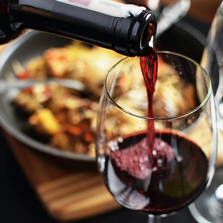 Rotwein wird in ein Glas eingeschenkt.