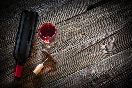 Rotweinflasche, Glas mit Wein und Korkenzieher auf Holztisch.