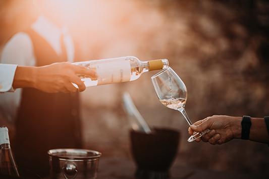 Weißwein wird in ein Glas eingeschenkt.