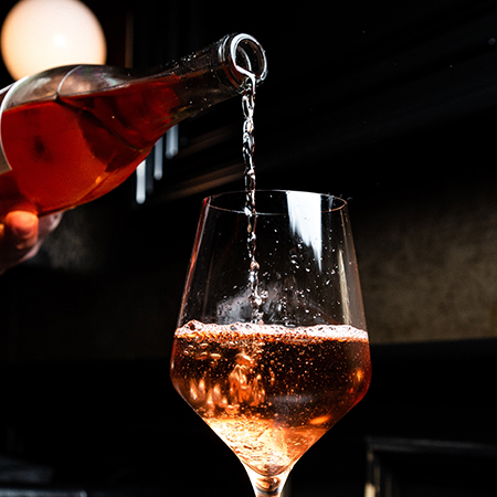 Rosé wird in ein Glas eingeschenkt.