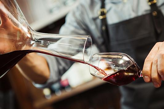 Rotwein wird aus einer Karaffe in ein Glas eingeschenkt.